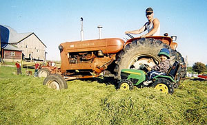 Uncle Jesse on full size tractor and one boy on his toy tractor